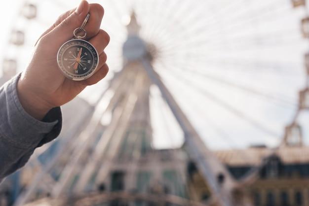 Primer plano de la mano humana que sostiene la brújula de navegación en el fondo de desenfoque de la rueda de la fortuna