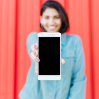 Primer plano de la mano humana que sostiene la pantalla en blanco móvil