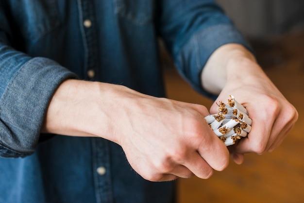 Primer plano de mano humana rompiendo paquete de cigarrillos
