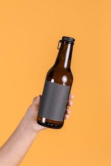 Primer plano de la mano humana sosteniendo una botella de cerveza marrón contra el fondo de la pared amarilla