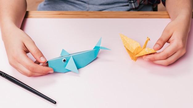 Primer plano de mano humana sosteniendo origami peces y aves