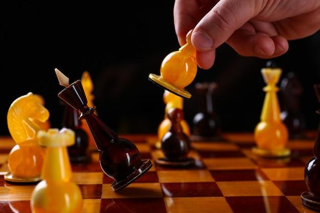 Primer plano de la mano del jugador moviendo la figura del ajedrez en la competencia. peones de mármol marrón y dorado a bordo. movimiento inteligente y táctico. juego de estrategia lógica y concepto de desafío de inteligencia