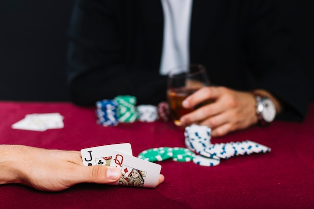 Primer plano de la mano de un jugador con un naipe en una mesa de póker roja