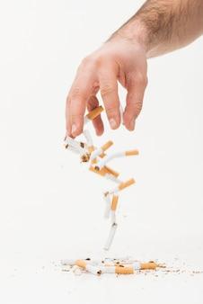 Primer plano de mano lanzando cigarrillos rotos sobre fondo blanco