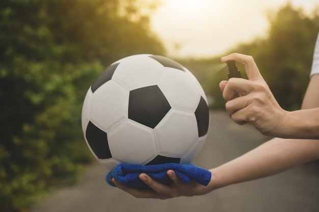 Primer plano de la mano limpieza con aerosol de alcohol el fútbol es normal y la liga de fútbol vuelve