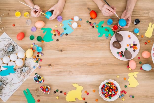 Primer plano de la mano de madre e hija pintando los huevos con pincel en el día de pascua