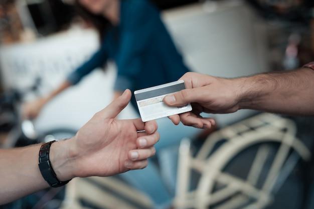 Primer plano de la mano masculina da la tarjeta de crédito al vendedor.