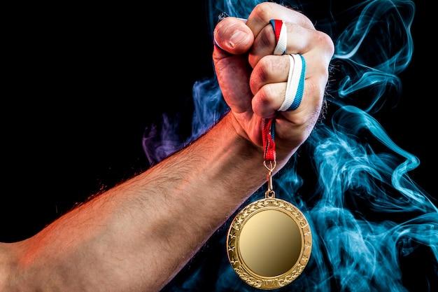 Primer plano de una mano masculina fuerte que sostiene una medalla de oro para un logro deportivo