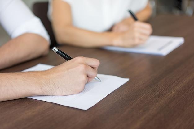 Primer plano de la mano masculina llenando el formulario de solicitud.