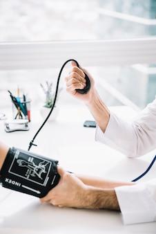 Primer plano de una mano masculina médico medir la presión arterial del paciente en la clínica