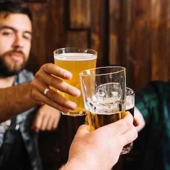 Primer plano de mano masculina tostado vasos de bebidas alcohólicas