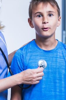 Primer plano de la mano de un médico examinando niño con estetoscopio