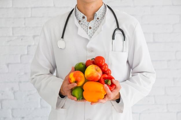 Primer plano de la mano del médico de sexo masculino con productos frescos frutas y verduras saludables