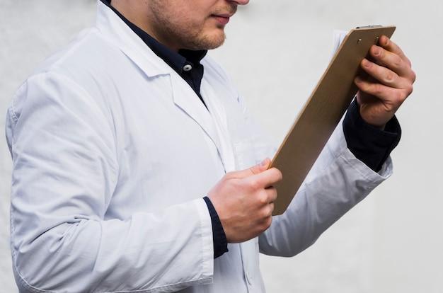 Primer plano de la mano de un médico de sexo masculino que lee el informe médico en el portapapeles