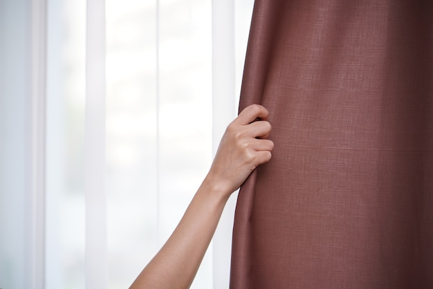 Primer plano de la mano de la mujer abriendo la cortina