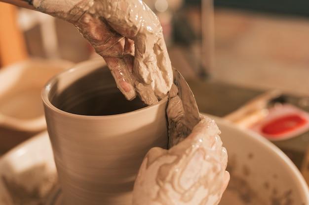 Primer plano de la mano de la mujer alisando el borde del jarrón con una herramienta plana