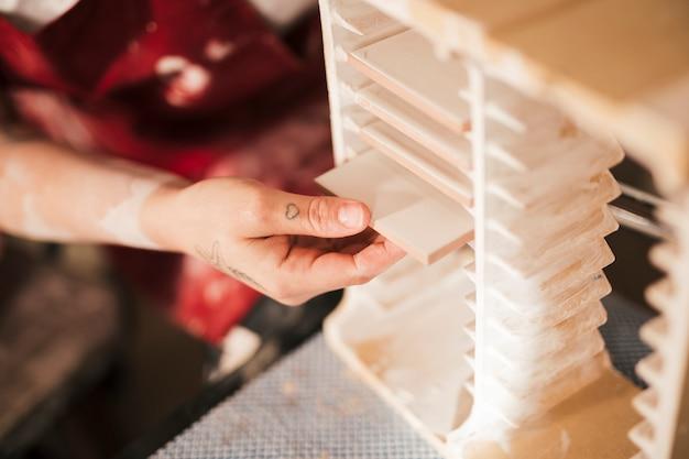 Primer plano de la mano de una mujer arreglando los azulejos pintados en el estante