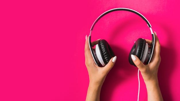 Primer plano de la mano de la mujer con auriculares en fondo rosa