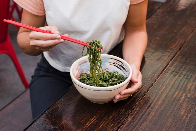 Primer plano de la mano de una mujer comiendo algas verdes con palillos rojos