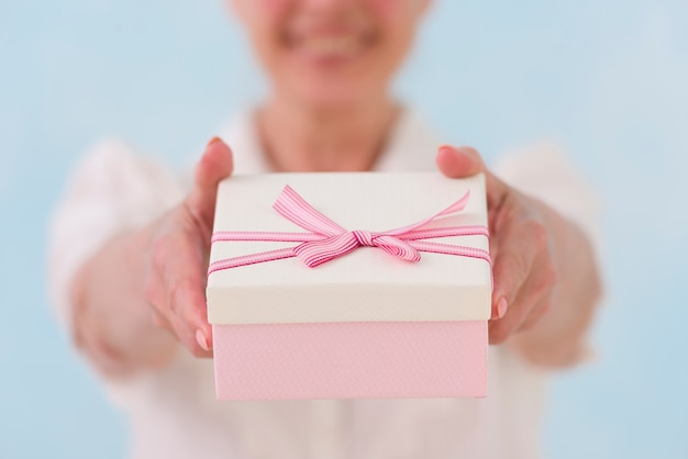 Primer plano de la mano de la mujer dando caja de regalo