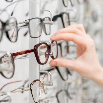 Primer plano de la mano de la mujer elige gafas en tienda de óptica
