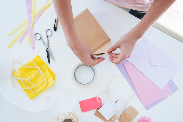 Primer plano de la mano de la mujer envolviendo la caja de regalo en la mesa