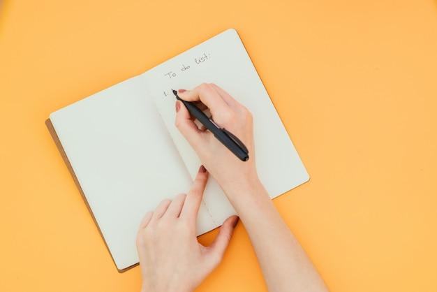 Primer plano de la mano de una mujer escribiendo una lista de tareas en un cuaderno limpio sobre una superficie naranja
