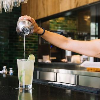 Primer plano de la mano de una mujer haciendo cóctel en barra de bar