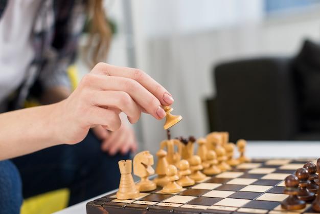 Primer plano de la mano de la mujer jugando el tablero de ajedrez de madera