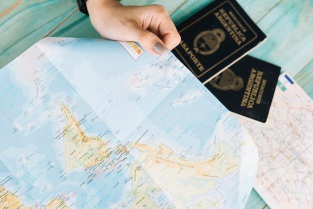 Primer plano de la mano de una mujer con mapa y pasaportes
