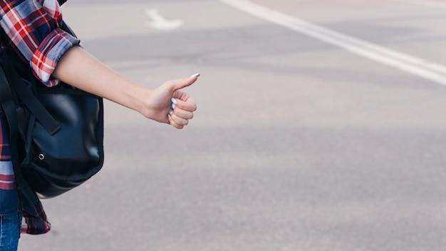 Primer plano de la mano de la mujer mostrando el pulgar hacia arriba gesto en la calle