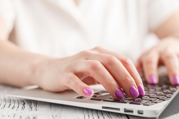 Primer plano de la mano de mujer de negocios con manicura escribiendo en el teclado del ordenador portátil