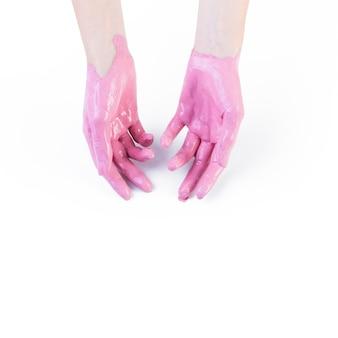 Primer plano de la mano de una mujer con pintura rosa sobre fondo blanco