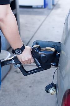 Primer plano de la mano de la mujer poniendo gas en el coche en la gasolinera