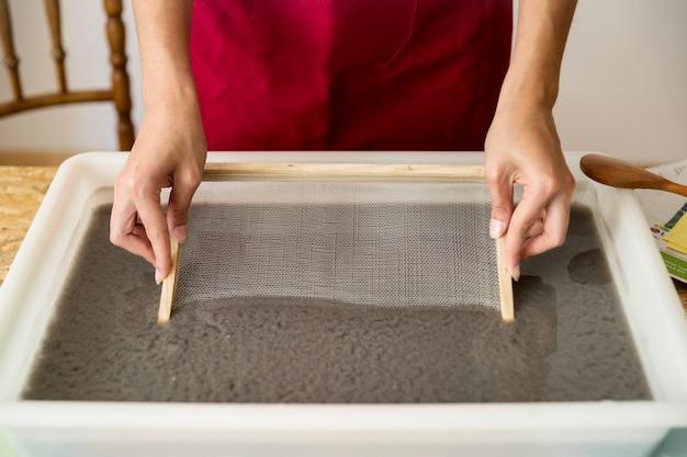 Primer plano de la mano de una mujer poniendo moho en la pulpa de papel