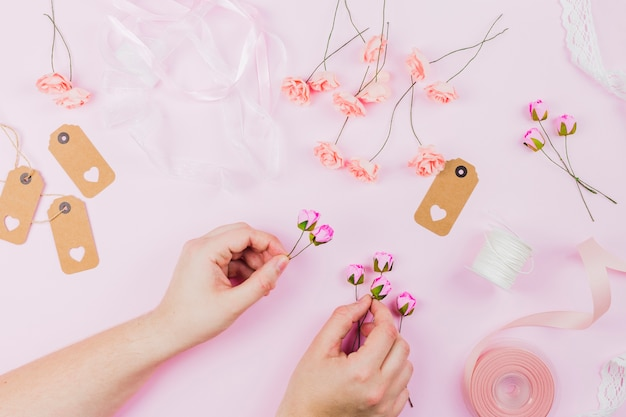 Primer plano de la mano de la mujer que arregla la flor contra el fondo rosado