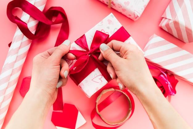 Primer plano de la mano de una mujer que ata la cinta roja en la caja de regalo sobre el fondo rosado