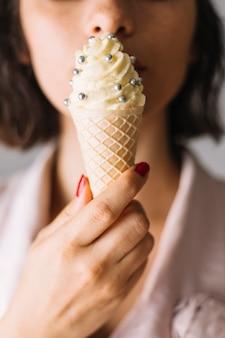 El primer plano de la mano de la mujer que come el cono de helado con plata asperja bolas