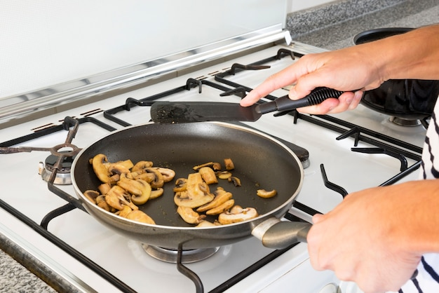 Primer plano de la mano de la mujer que fríe las rebanadas de la seta en la cacerola sobre la estufa de gas