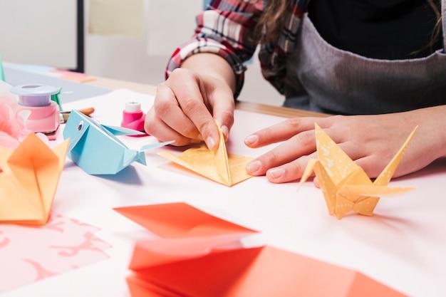 Primer plano de la mano de la mujer que hace arte creativo del arte usando el papel del origami