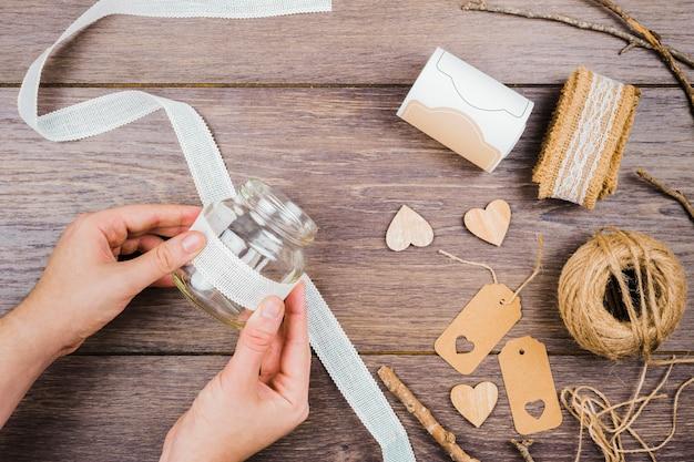 Primer plano de la mano de la mujer que pega la cinta de encaje blanco en una botella de vidrio sobre el escritorio de madera