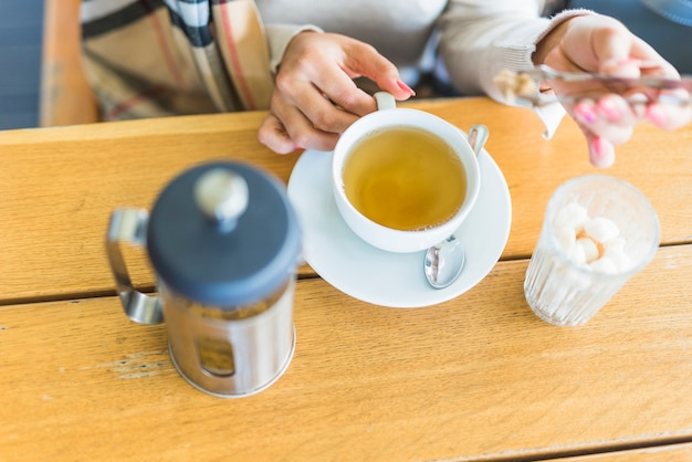 Primer plano de la mano de una mujer que pone azúcar moreno con las pinzas en el té de hierbas en la mesa de madera
