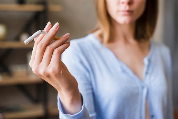 Primer plano de la mano de la mujer que sostiene el cigarrillo roto