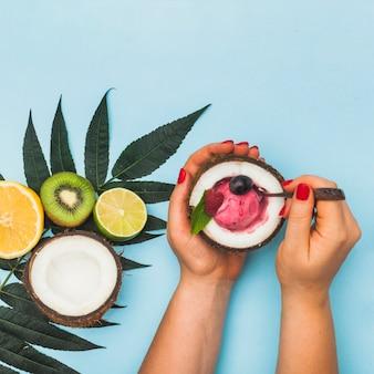 Primer plano de la mano de una mujer que sostiene helado de fruta congelada dentro del coco reducido a la mitad