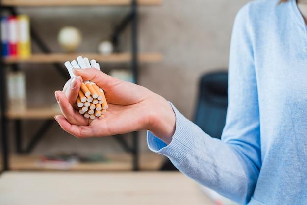 Primer plano de la mano de la mujer que sostiene el manojo de cigarrillo