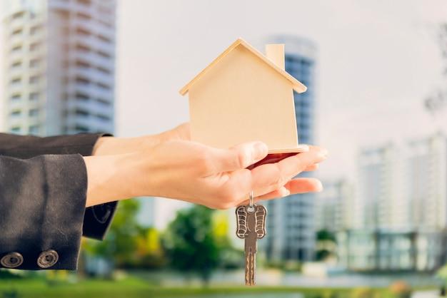 Primer plano de la mano de la mujer que sostiene el modelo de la casa de madera y las llaves contra el telón de fondo borroso