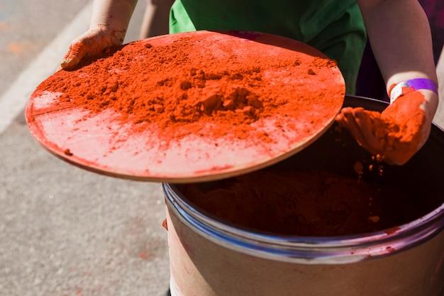 Primer plano de la mano de la mujer que toma polvo de color holi del tambor