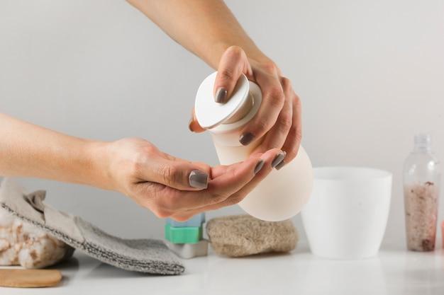 Primer plano de la mano de una mujer que vierte jabón desinfectante del dispensador con producto de spa en el escritorio blanco contra el fondo