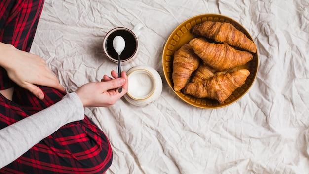Primer plano de la mano de la mujer que vierte la leche en polvo en la taza de té con croissant horneado en la sábana desmenuzada