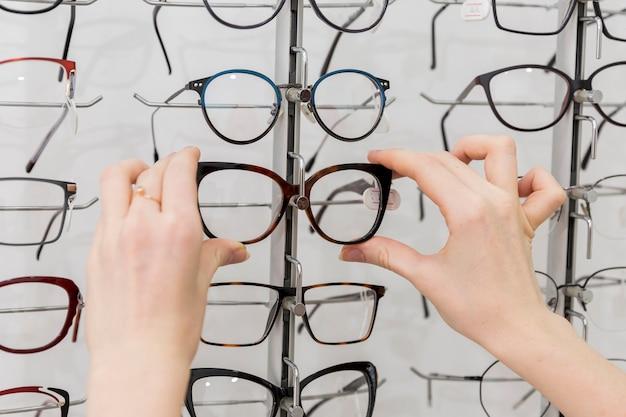 Primer plano de mano de mujer quitando anteojos de la pantalla